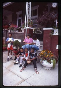 Photograph of Residents relax on the steps of a rowhouse, Baltimore MD, September 1985. Photo ID: na059. North Avenue Collection (R0090-NA), University of Baltimore Special Collections & Archives.