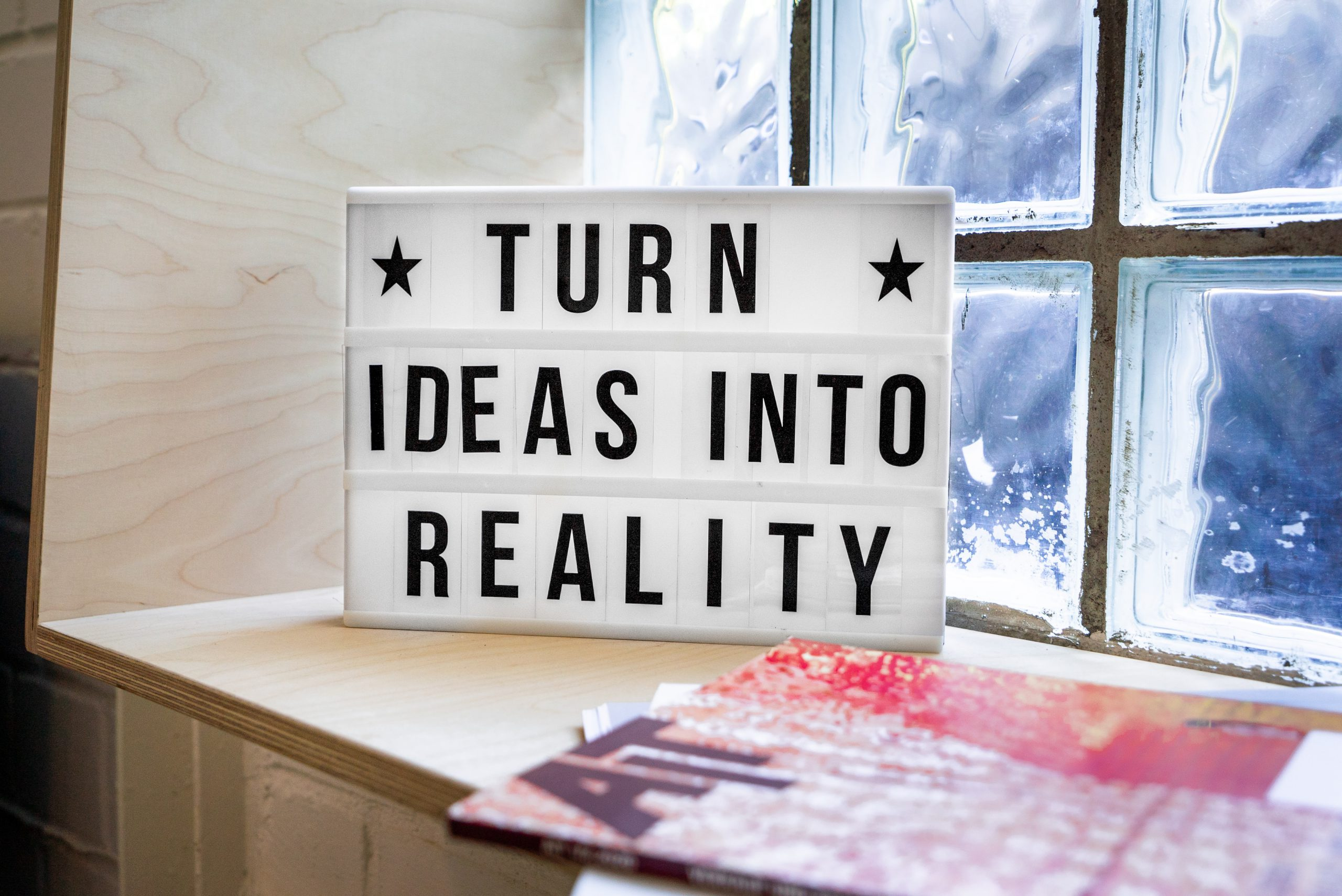 """white and black wooden quote board with inspirational quote """"turn ideas into reality"""""""